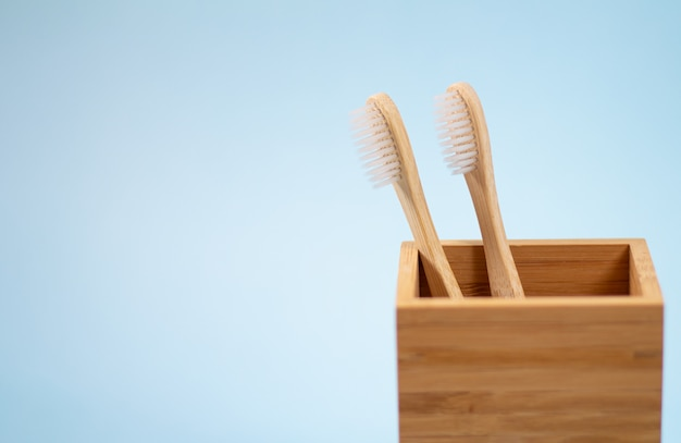 Duas escovas de dentes de bambu ecológicas em suporte de madeira sobre fundo azul claro, com espaço para texto