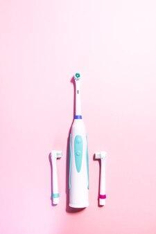 Duas escovas de dentes elétricas em um fundo rosa claro suave.