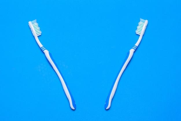 Duas escovas de dentes em um fundo azul. a vista do topo. postura plana.