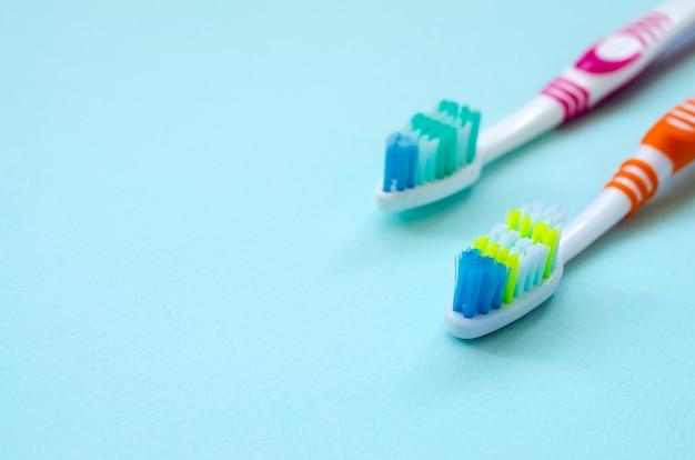 Duas escovas de dentes mentem sobre um fundo azul pastel