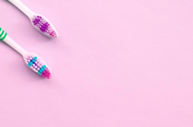 Duas escovas de dentes mentem sobre um rosa pastel