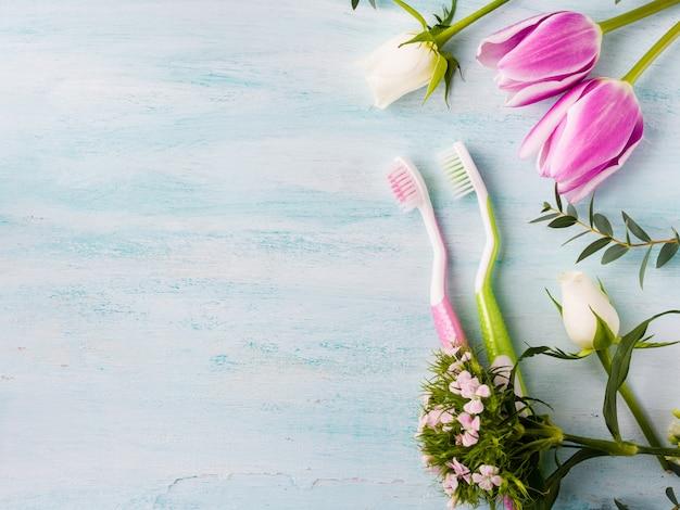 Duas escovas de dentes pastel com ervas de flores