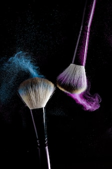 Duas escovas para maquiagem com sombras de maquiagem azul e rosa em movimento em um fundo preto.