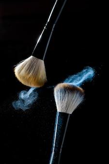 Duas escovas para maquiagem com sombras de maquiagem azul em movimento em um fundo preto.