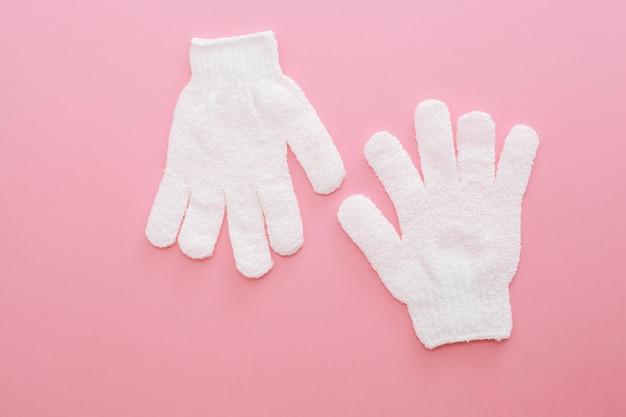 Duas esfoliantes luva de massagem para banho em fundo rosa. luvas para uso no chuveiro para massagem e esfoliação.