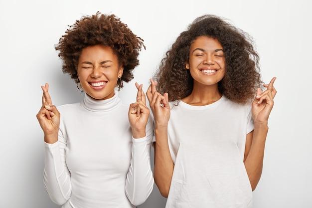 Duas esperançosas mulheres afro-americanas oram, mantêm os dedos cruzados, sorriem amplamente, vestidas com roupas casuais brancas, antecipam resultados positivos, ficam próximas uma da outra.