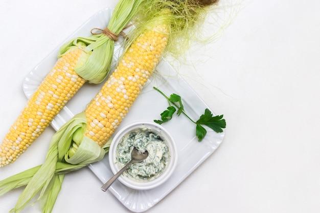 Duas espigas de milho fresco e uma tigela de molho na chapa branca. copie o espaço. fundo branco. postura plana