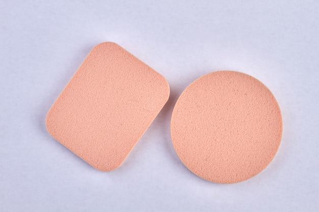 Duas esponjas cosméticas isoladas em branco. esponjas de base cosmética de maquiagem bege em branco.