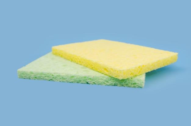 Duas esponjas de limpeza coloridas isoladas em um fundo azul