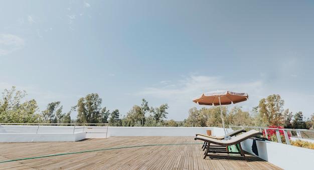 Duas espreguiçadeiras ao sol e guarda-sol no estrado de madeira com o céu azul