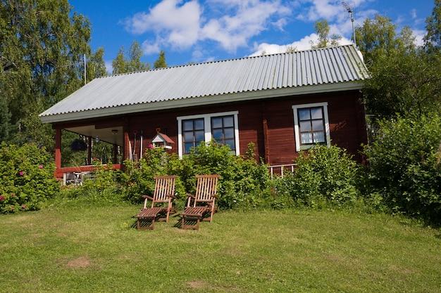 Duas espreguiçadeiras de madeira e tradicional casa de campo finlandesa na vila.