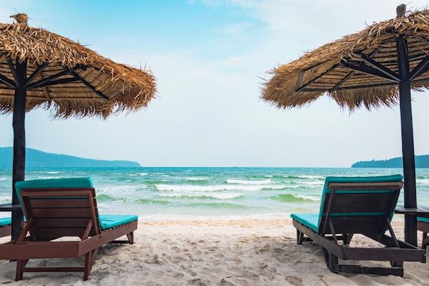 Duas espreguiçadeiras e guarda-chuva de palha na praia tropical. costa da ilha de koh rong samloem, camboja. cópia vazia espaço livre para texto