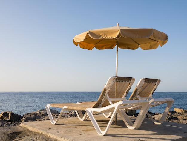 Duas espreguiçadeiras e um guarda-sol em pé no quebra-mar com vista para o oceano atlântico, porto rico, nas ilhas canárias