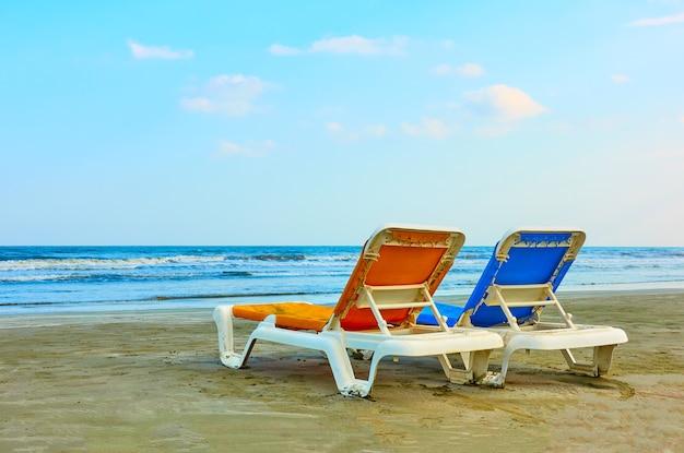 Duas espreguiçadeiras em uma praia de areia