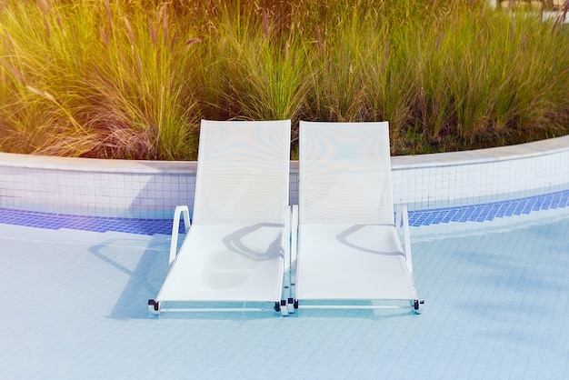 Duas espreguiçadeiras na água estão na piscina. hotel, férias de verão.
