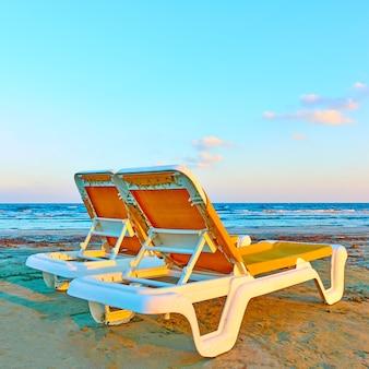 Duas espreguiçadeiras vazias em uma praia de areia