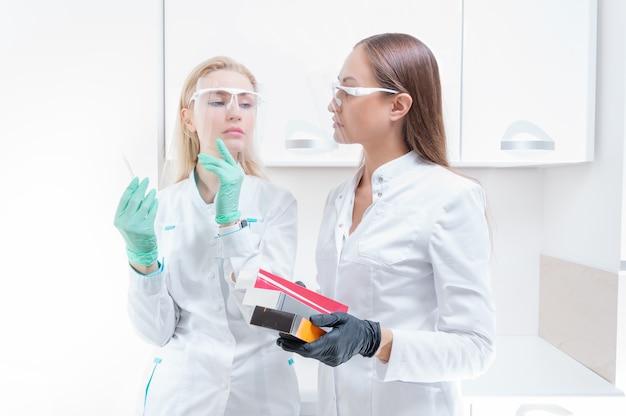 Duas esteticistas posam em um consultório médico com preparações cosméticas e uma seringa. conceito de rejuvenescimento da pele. mídia mista