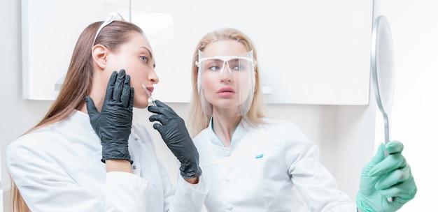 Duas esteticistas posam em um salão médico com um espelho nas mãos. conceito de rejuvenescimento. mídia mista