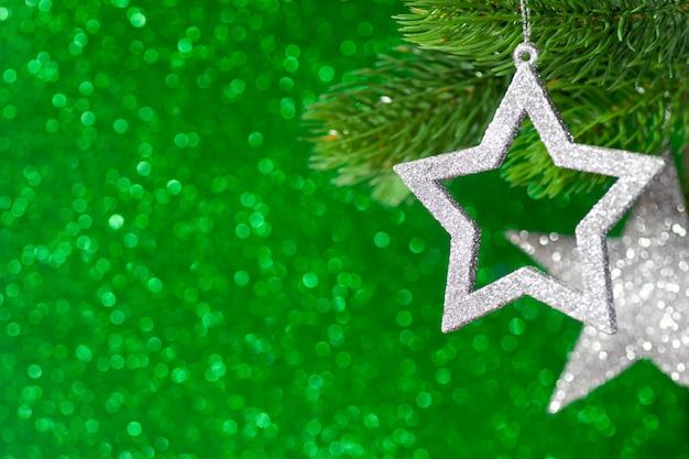 Duas estrelas de prata em um galho de árvore de natal em um fundo verde brilhante de bokeh