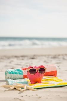 Duas estrelas do mar e banco piggy com óculos de sol na praia cobertor
