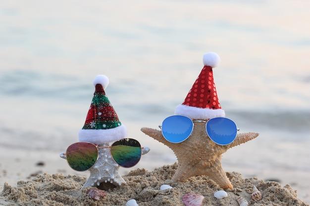 Duas estrelas do mar na praia do mar com óculos escuros e chapéu de papai noel para feliz natal e ano novo