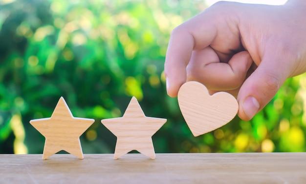 Duas estrelas e coração em um fundo verde do bokeh. classificação de três estrelas, a escolha