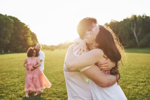 Duas famílias de diferentes gerações se abraçam. jovem marido e mulher, bem como seus pais antigos que ainda se amam