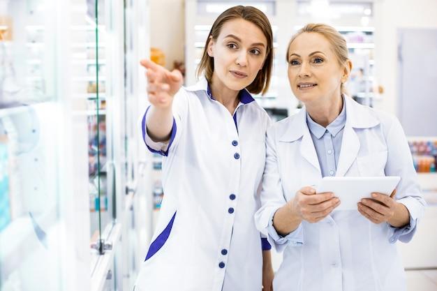 Duas farmacêuticas atentas e experientes discutindo uma variedade na frente de uma vitrine de remédios