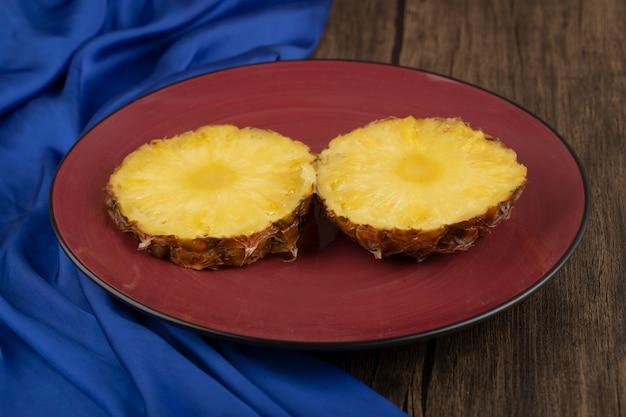 Duas fatias de abacaxi maduro fresco colocadas sobre uma mesa de madeira.