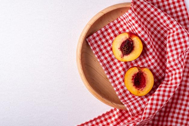 Duas fatias de frutos de nectarina pêssego com sementes em placa de madeira com toalha de mesa quadriculada vermelha em fundo branco, cópia espaço, vista superior, vista plana