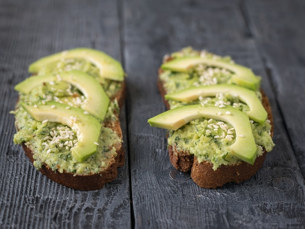 Duas fatias de pão de farinha de trigo manchada com creme de abacate com ervas. uma dieta vegetariana.