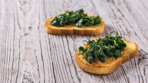 Duas fatias de pão frito com verduras fritas em uma mesa de madeira. lanche vegetariano.