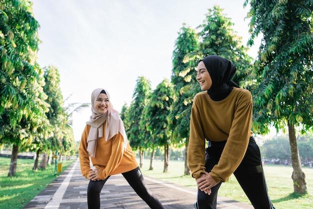 Duas felizes garotas muçulmanas com lenço na cabeça dão investidas antes de correr e praticar esportes ao ar livre