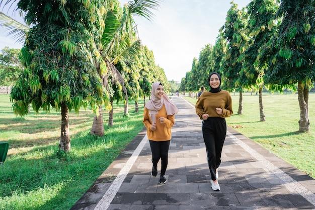 Duas felizes garotas muçulmanas com lenço na cabeça praticam esportes ao ar livre enquanto correm juntas no parque