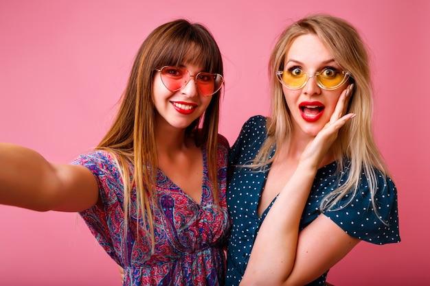 Duas felizes melhores amigas, irmãs, mulheres, garotas, usando vestidos da moda primavera-verão com estampas vintage brilhantes e óculos escuros