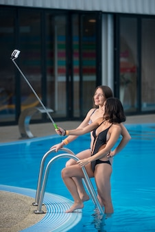 Duas fêmeas de biquíni posando contra a piscina