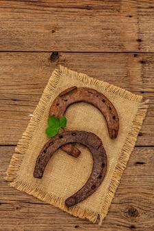 Duas ferraduras muito velhas do cavalo do metal do ferro fundido, folha fresca do trevo. símbolo de boa sorte, conceito do dia de st.patrick