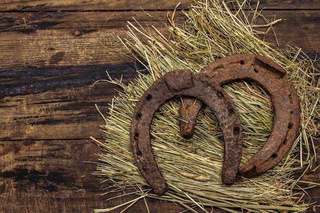 Duas ferraduras muito velhas do cavalo do metal do ferro fundido no feno. símbolo de boa sorte, conceito do dia de st patrick. fundo de madeira antigo