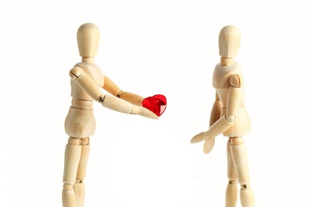 Duas figuras de madeira de um boneco, dão um coração vermelho, isolado em uma superfície branca - fotos dos conceitos do tema amor e dia dos namorados