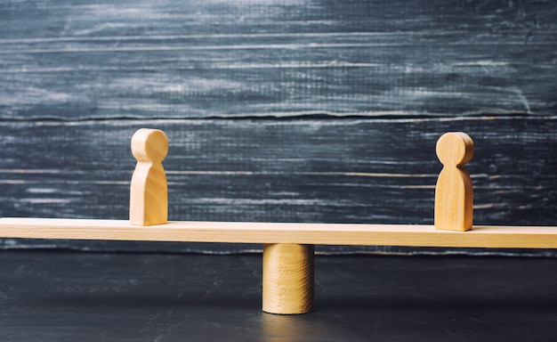 Duas figuras de madeira estão na balança da justiça