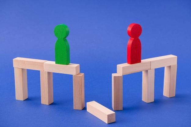 Duas figuras de madeira solitárias empresários em pé na ponte quebrada