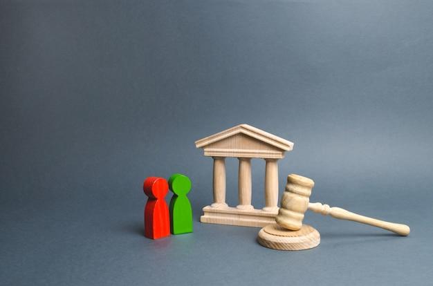 Duas figuras de oponentes estão perto do tribunal e do martelo do juiz. resolução de conflitos