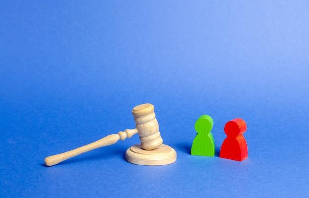 Duas figuras de pessoas oponentes estão perto do martelo do juiz.