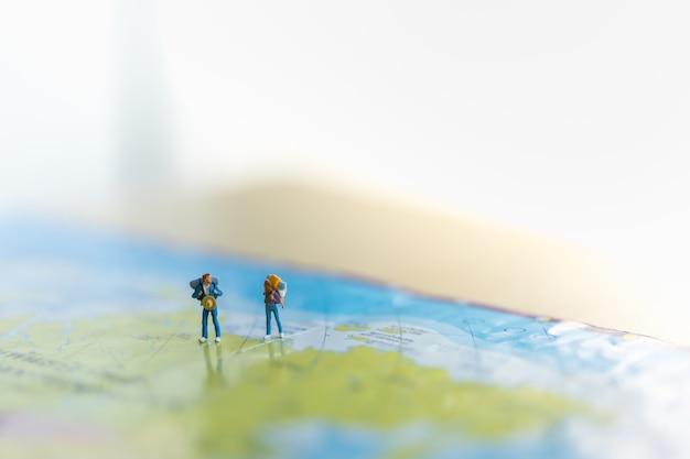 Duas figuras em miniatura com mochila em pé no mapa do mundo