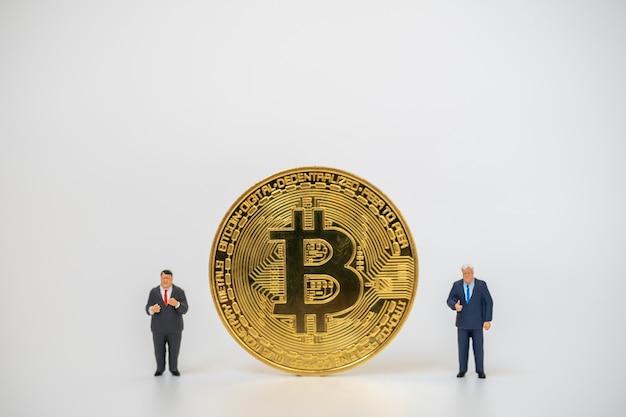 Duas figuras em miniatura de empresário pessoas em pé com moedas de ouro de bitcoin no fundo branco