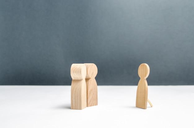 Duas figuras humanas olham para uma falsa figura humana