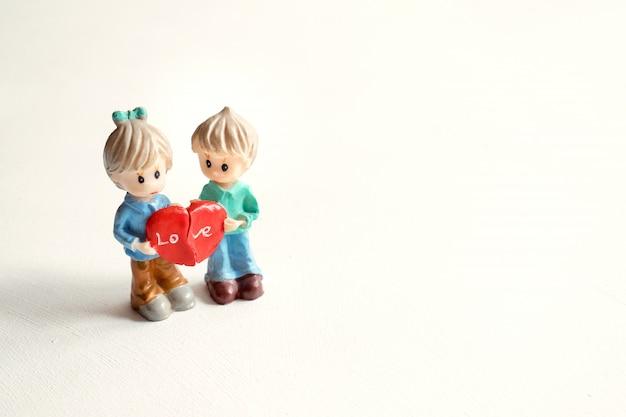 Duas figuras menino e menina com as metades do coração vermelho
