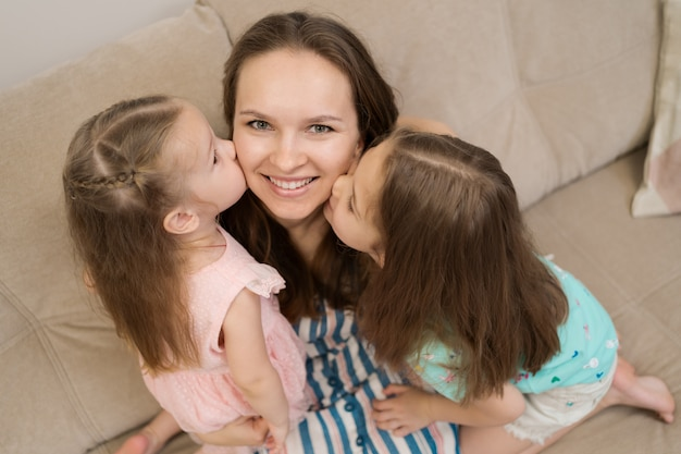 Duas filhas beijando sua mamãe