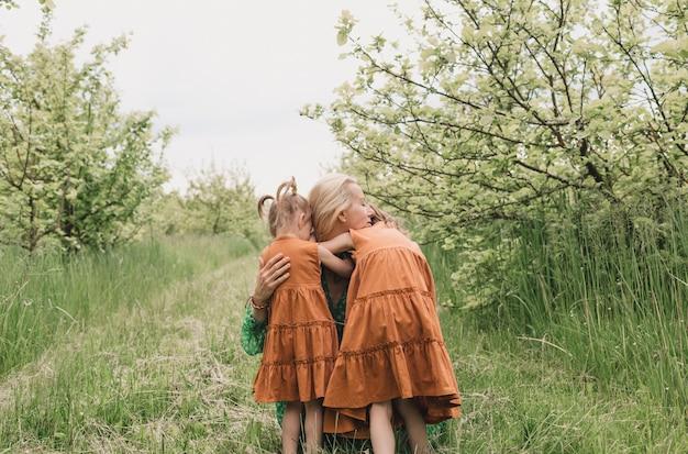 Duas filhas em vestidos idênticos abraçam uma mãe feliz em um pomar de maçãs