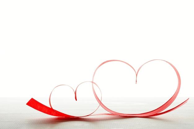 Duas fitas vermelhas em forma de coração na mesa